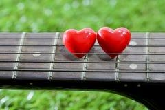 Coeur sur des guitares de cou et ficelles sur l'herbe Images stock