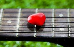 Coeur sur des guitares de cou et ficelles sur l'herbe Photographie stock