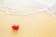 Coeur sur la plage de sable avec la lumière chaude de vague molle Photo stock