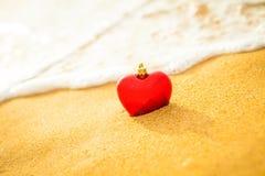 Coeur sur la plage de sable avec la lumière chaude de vague molle Images libres de droits
