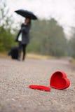 Coeur sur la route et la femme avec le bagage et le parapluie à l'arrière-plan Image stock