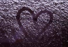 Coeur sur le pare-brise couvert de neige de voiture Photo stock