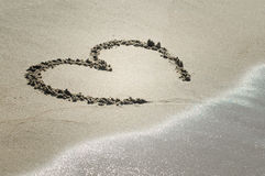 Coeur sur le sable avec l'approche d'onde image stock