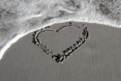 Coeur sur le sable blanc noir Image libre de droits