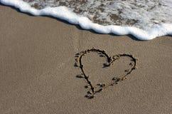 Coeur sur le sable de plage Photos stock