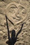 Coeur sur le sable et l'ombre de l'enfant Images stock