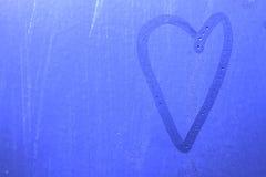 Coeur sur le verre de rosée bleu Photo libre de droits