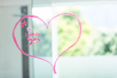 Coeur sur un miroir écrit avec le rouge à lèvres rose Photos stock