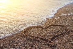Coeur sur un sable de plage avec la vague sur le fond image libre de droits