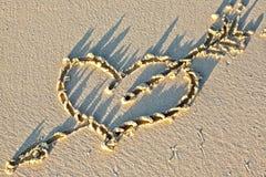 Coeur sur une plage sablonneuse Photos stock