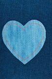 Coeur symbolique fait de jeans se trouvant sur les jeans foncés Photo stock