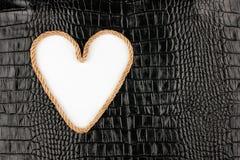Coeur symbolique fait en corde se trouvant sur un cuir de crocodile Image libre de droits