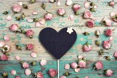Coeur-tableau noir avec de petites fleurs roses sur le vieil OE de turquoise Photos libres de droits