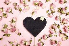 Coeur-tableau noir vide avec de petites roses sèches sur le fond rose Images stock