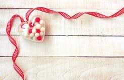 Coeur transparent avec les pilules douces de sucrerie, ruban, ` s DA de valentine Image stock