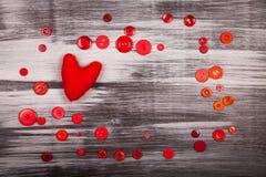 Coeur tricoté par rouge et beaucoup de boutons rouges Photo libre de droits