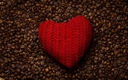 Coeur tricoté par rouge se trouvant sur des grains de café Images stock