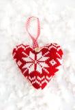 Coeur tricoté sur la neige Photos stock