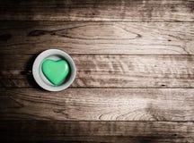 Coeur vert en céramique dans la tasse de café Images libres de droits