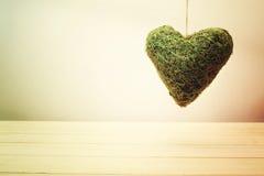 Coeur vert rustique de mousse à un arrière-plan beige de mur de gradient Photos stock