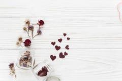 Coeurs élégants dans le pot en verre et configuration plate de roses sur b en bois blanc Photos stock