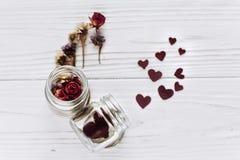 Coeurs élégants dans le pot et les roses en verre sur le CCB en bois blanc rustique Photo stock