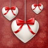 Coeurs accrochés avec l'arc rouge pour le jour du ` s de Valentine Photographie stock libre de droits