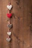 Coeurs accrochant sur le mur en bois Photo stock