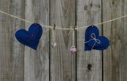 Coeurs bleus et rouges et serrures de tissu accrochant sur la corde à linge par le fond en bois rustique Image stock