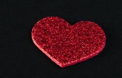 Coeurs brillants rouges sur le fond noir Image stock