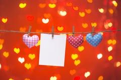 Coeurs colorés accrochant sur la corde à linge avec la carte vierge Photo stock