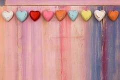 Coeurs colorés d'amour sur le conseil peint Image libre de droits