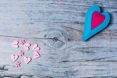 Coeurs colorés de feutre fabriqué à la main sur le fond en bois Image libre de droits
