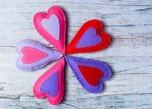 Coeurs colorés de feutre fabriqué à la main sur le fond en bois Photo libre de droits