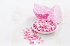 Coeurs colorés de sucre et plats de papier de cuisson Image stock