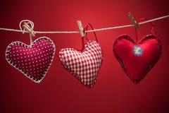 Coeurs colorés de tissu sur les milieux rouges Photo libre de droits