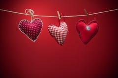 Coeurs colorés de tissu sur les milieux rouges Photographie stock
