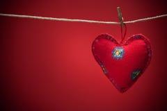 Coeurs colorés de tissu sur les milieux rouges Images stock