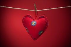 Coeurs colorés de tissu sur les milieux rouges Photo stock