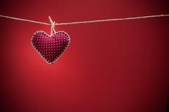 Coeurs colorés de tissu sur les milieux rouges Image libre de droits