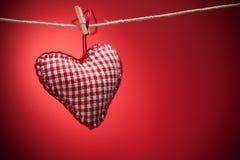 Coeurs colorés de tissu sur les milieux rouges Images libres de droits
