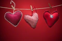 Coeurs colorés de tissu sur les milieux rouges Photographie stock libre de droits