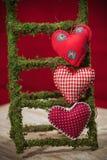 Coeurs colorés de tissu sur les milieux rouges Photos libres de droits