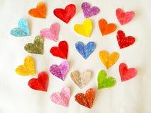 Coeurs colorés sur le fond de livre blanc Photographie stock libre de droits
