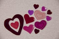 Coeurs colorés sur le papier rose Photos stock