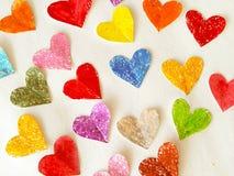 Coeurs colorés sur le plan rapproché de fond de livre blanc Photographie stock