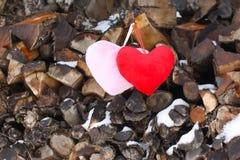 Coeurs décoratifs sur la pile de bois de chauffage Image libre de droits
