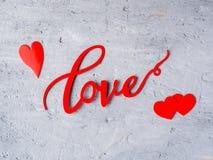 Coeurs d'AMOUR et de papier d'inscription sur un fond concret de l'espace de copie de jour du ` s de Valentine Images stock
