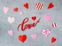 Coeurs d'AMOUR et de papier d'inscription sur un fond concret de l'espace de copie de jour du ` s de Valentine Photographie stock