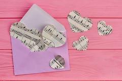 Coeurs d'enveloppe et de papier avec des notes de musique Photo stock